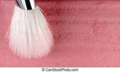 Blush brush gains pink dry pigment on pile to be used in make-up. Artist working with face palette. Details of working process, tools in beauty industry. Decorative cosmetics. High quality 4k footage