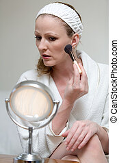 Woman looking in the mirror holding a blush brush applying blush