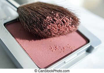 A macro shot of a blusher compact with a brush. Shallow depth of field.