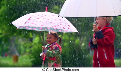 Blustery and Chilly - Kids standing under umbrellas in heavy...