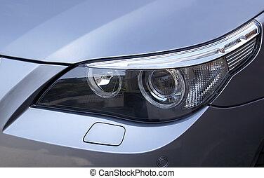 BMW Headlight - Headlight on a silver metallic BMW Saloon