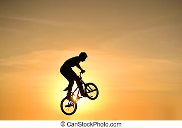 BMX action - bmx rider action against sky at sunset.