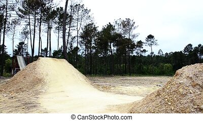 BMX biker jumping dirt jumps track.