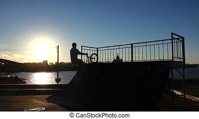 BMX biker. Trick on skate park. Silhouette against a...