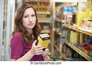 boîte, femme, vérification, supermarché, nourriture, étiquetage, portrait