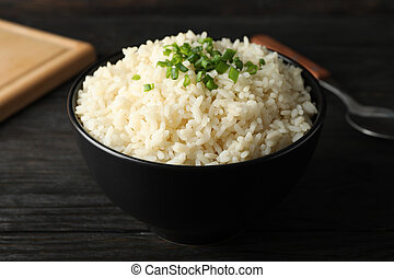 Board, bowl of delicious rice and spoon on wooden background, close up