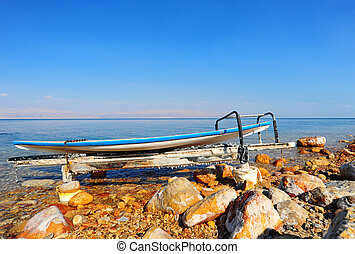 Board for windsurfing covered in salt on the beach of the Dead Sea.