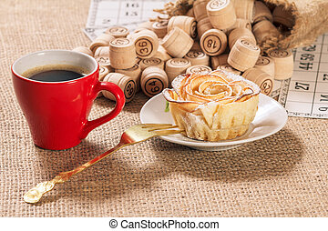 Board game lotto on sackcloth. Wooden lotto barrels in bag and game cards with cup of coffee and homemade cookie on plate.