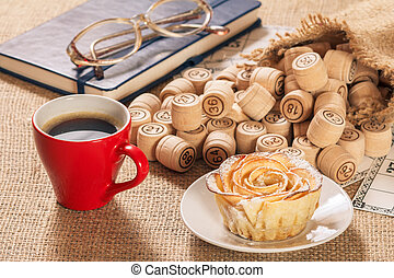 Board game lotto on sackcloth. Wooden lotto barrels in bag and game cards with notebook, cup of coffee and homemade cookie.