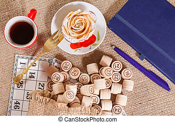 Board game lotto on sackcloth. Wooden lotto barrels in bag and game cards with notebook, pen, cup of coffee and homemade cookie.