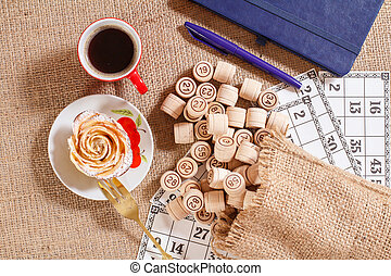 Board game lotto on sackcloth. Wooden lotto barrels in bag and game cards with notebook, pen, cup of coffee and homemade cookie on plate.