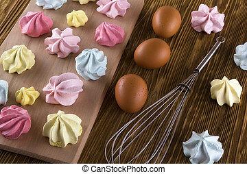 Board of homemade pastel colored meringue cookies.