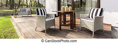 Modern board terrace in scandynavian style in the backyard of a white house