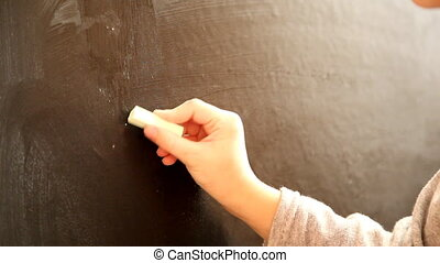 Board - child writes on the chalk board