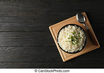 Board with bowl of delicious rice on wooden background, top view