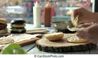 Board with sliced burger bun. Guy making a sandwich.