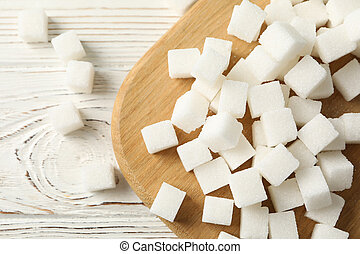 Board with sugar cubes on wooden background, top view