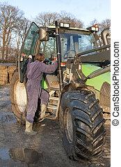 Boarding a tractor - Farm hand boarding a big tractor