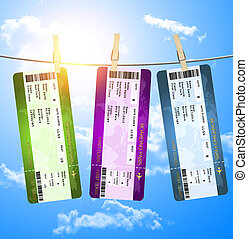 boarding pass tickets hanging on clothesline over blue sky -...