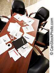 Empty boardroom: black chairs around table with business objects on it
