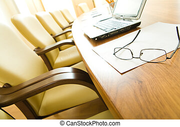 Image of table with laptop, papers, glasses on it with chairs near by in row