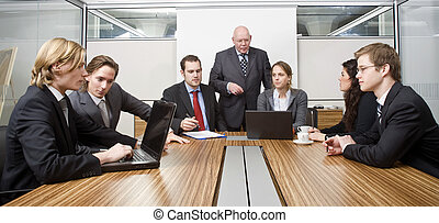 Seven people in a cubicle, preparing for a management team meeting