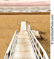 Boardwalk on the beach at sunset