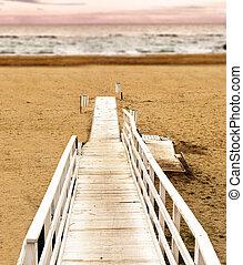 Boardwalk on the beach at sunset