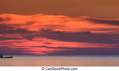 Boat along Horizon against Red Clouds in Dark Sky after Sunset