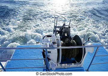 Boat anchor winch pulley and rope. Prop wash foam and evening sun reflexion