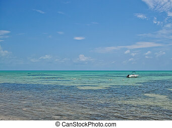 Florida Keys - boat anchored in the shallow waters off the...