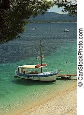 Boat anchorer on beach - Boat anchored near sandy beach in...
