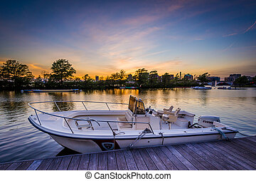 Boat and dock at sunset at the Charles River Esplanade, in Boston, Massachusetts.
