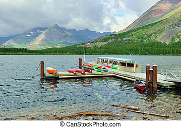 boat and kayaks in swiftcurrent lake in Glacier National...