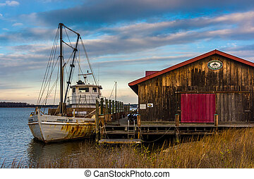 Boat and old building on the shore of the Chesapeake Bay, in...