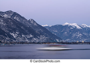 Boat and snow-capped mountains in blue hour