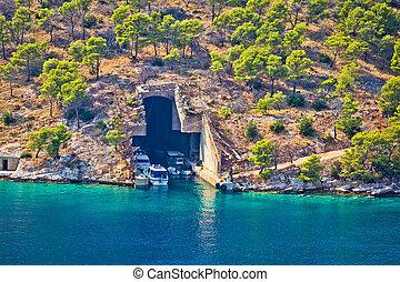 Boat and submarine shelter on Brac island stone coast,...