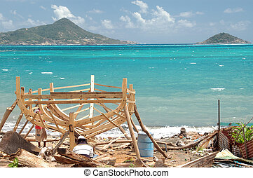 boat being built by hand with petite martinique in background