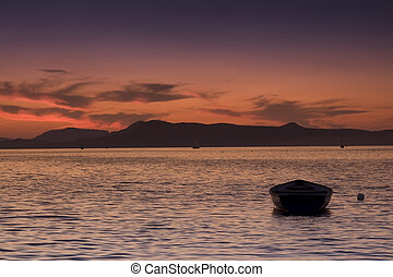 boat by the lake at sunset