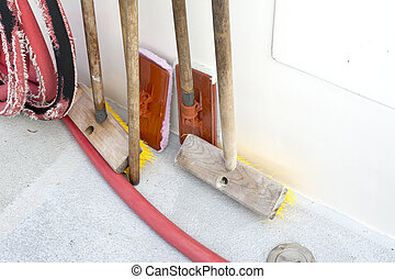 A set of boat deck cleaning and scrubbing supplies propped up against the hull