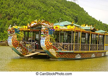 Boat cruise dragon heads on the Perfume River in Hue. The boats often have a portrait of the dragon or a symbolic point reminding of the mythical animal in the country, such as an eye, a red or yellow stripe.