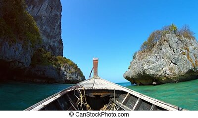 Boat Cruising beneath Limestone Cliffs on a Tropical Sea -...