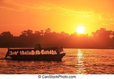 Boat cruising the Nile river at sunset, Luxor, Egypt