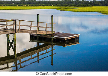 On a calm morning, a boat dock reflects in the blue waters of an inlet along the Atlantic Coast