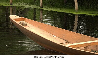 Boat drifting through placid water - The back end of a canoe...
