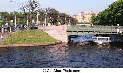 Boat floats under 2-nd Garden Bridge over channel in center...