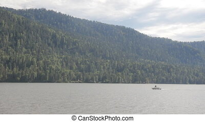 boat goes along the shore of a mountain lake. Teletskoye in...