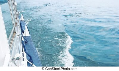 Boat in motion, blue water.