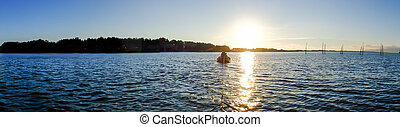 Boat in the ocean with sunset panorama