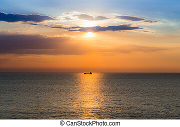 Boat in the ocean with sunset sky background